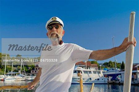 Croatia, Senior man with captain's hat on sailboat