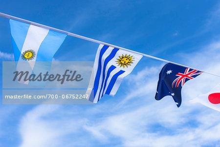 Uruguayan, Argentinian, Australian, and Japanese flags against blue summer sky