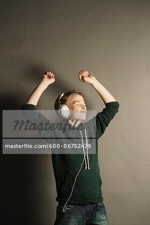 Boy Listening to Music with Headphones, Studio Shot