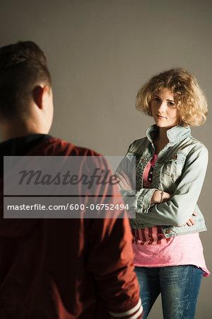 Teenage Girl with Arms Crossed looking at Teenage Boy, Studio Shot