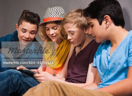 Teenagers looking at Tablet PC, Studio Shot