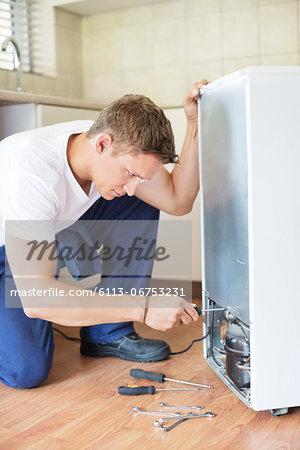Repairman working on appliance in kitchen