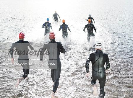 Triathletes in wetsuits running into ocean