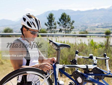 Man adjusting bicycle outdoors
