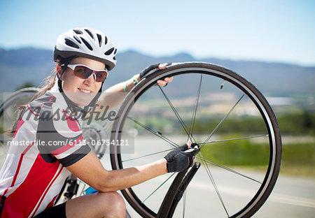 Cyclist adjusting tires on rural road
