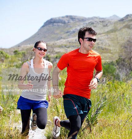 Couple running on dirt path