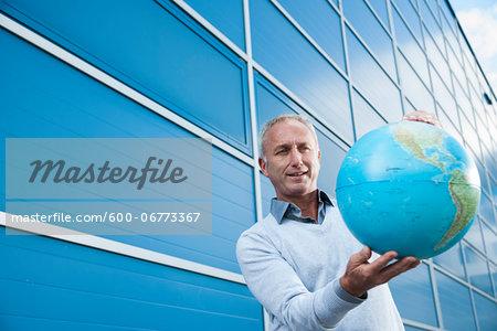 Businessman Holding Globe Outdoors, Mannheim, Baden-Wurttemberg, Germany