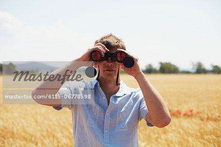 Man On Field Looking Through Binoculars, Croatia, Dalmatia, Europe