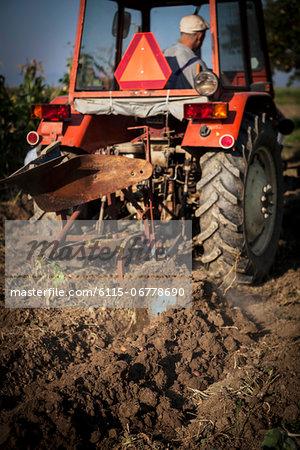Farmer In Tractor Ploughing Field, Croatia, Slavonia, Europe