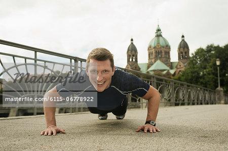 Young man doing push-ups on bridge, Munich, Bavaria, Germany