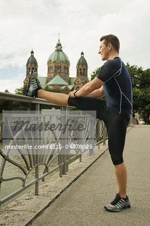 Young man stretching on bridge, Munich, Bavaria, Germany