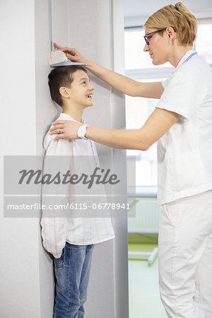 Female doctor measuring boys height, Osijek, Croatia