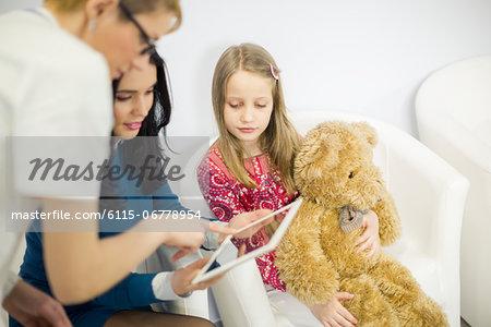 Female doctor and woman looking at digital tablet, girl holding a teddy bear, Osijek, Croatia