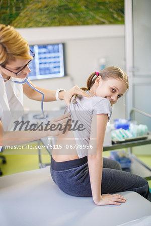 Female doctor using stethoscope on girl, Osijek, Croatia