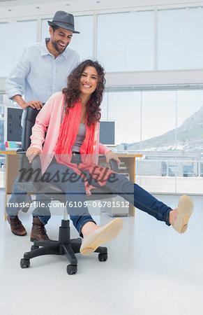 Creative business colleagues having fun on a swivel chair