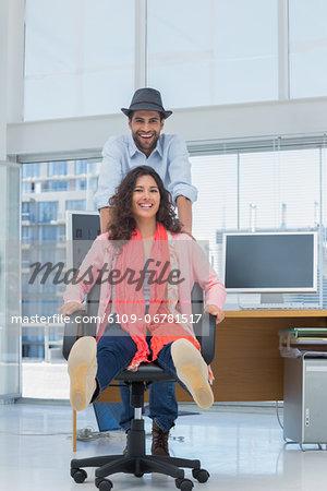 Photo editors having fun on a swivel chair