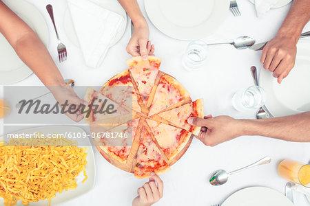 Hands choosing slice of pizza