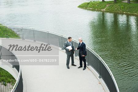 Mature businessmen standing on walkway talking, Mannheim, Germany