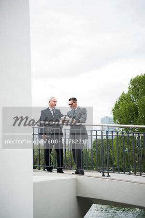 Mature businessmen standing on outdoor bridge talking, Mannheim, Germany
