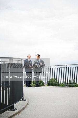 Mature businessmen standing on bridge, Mannheim, Germany