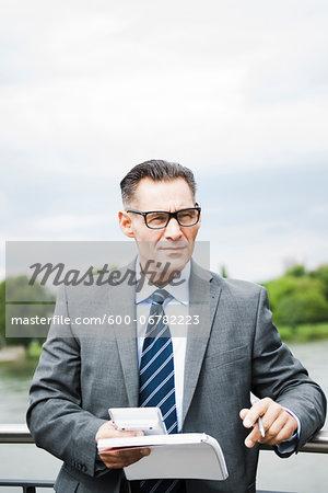 Portrait of mature businessman standing on bridge holding documents, wearing horn-rimmed eyeglasses, Mannheim, Germany