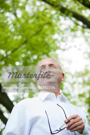 Close-up portrait of mature man holding horn-rimmed eyeglasses in park, Mannheim, Germany