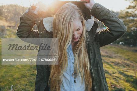 Young woman putting on her hood, Hood River, Oregon, USA