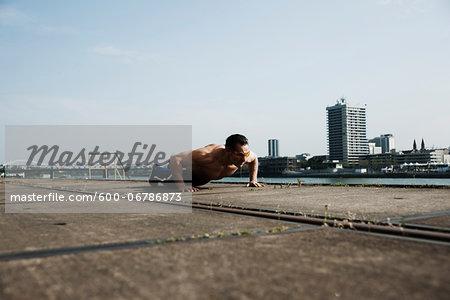 Mature man doing push-ups on loading dock, Mannheim, Germany