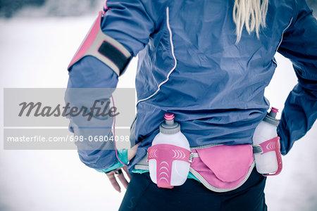 Midsection of woman wearing water bottle belt in winter
