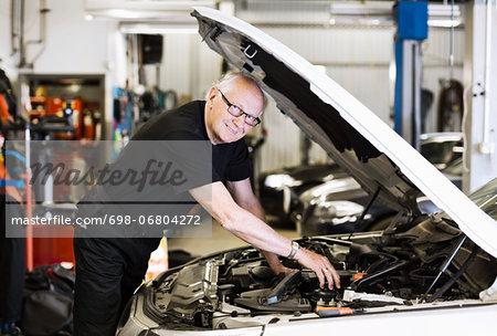 Portrait of confident male mechanic working under car bonnet in workshop