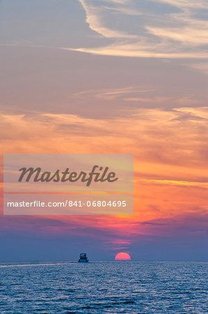 Boat driving into the sunset at Zlatni Rat Beach, Bol, Brac Island, Dalmatian Coast, Adriatic, Croatia, Europe