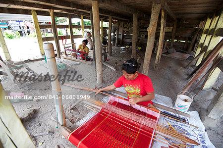 Batak woman weaving Batak Toba design sarong beneath her traditional Batak house, Buhit, Samosir Island, Lake Toba, Sumatra, Indonesia, Southeast Asia, Asia