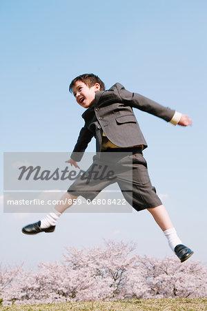 Young boy in school uniform jumping on grassland