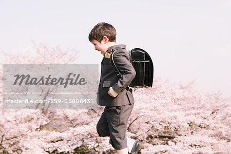 Young boy in school uniform walking