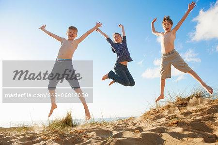 Boys and teenage girl jumping on beach