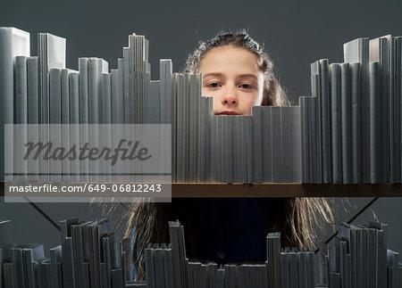 Girl peeking between books on bookshelf