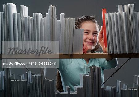 Girl choosing red book from bookshelf