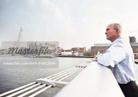 Mature man leaning on Millennium Bridge, London, England, UK
