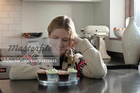 Woman kneeling admiring self-made cupcakes