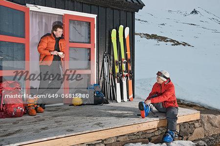 Couple outside chalet with skis, Klaengsholl, Skidadalur, Dalvik, Iceland