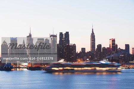 Manhattan skyline and cruise boat at dusk, New York City, USA