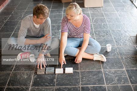 Young couple sitting on floor choosing new tiles