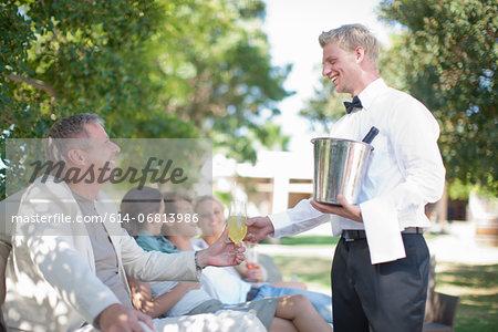 Waiter serving customers in garden