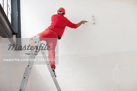 Decorator straddling step ladder
