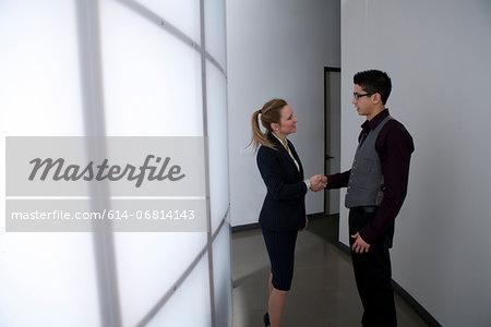 Young businesspeople in corridor shaking hands