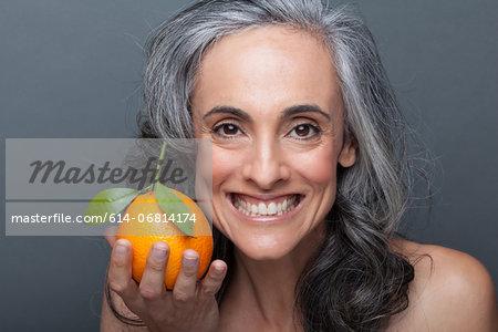 Mature woman holding orange