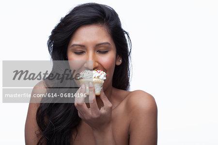Young woman eating cupcake
