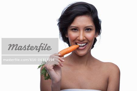 Young woman biting carrot