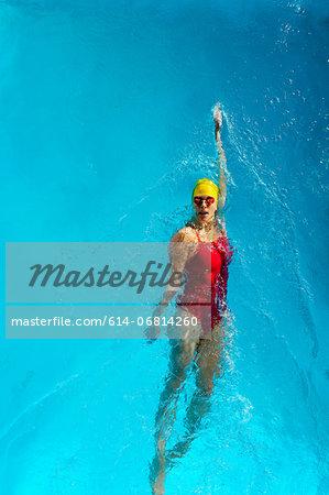 Mature woman doing backstroke in swimming pool