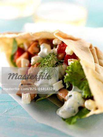 Chicken,tomato,feta and lettuce pitta bread sandwich with white yoghurt sauce